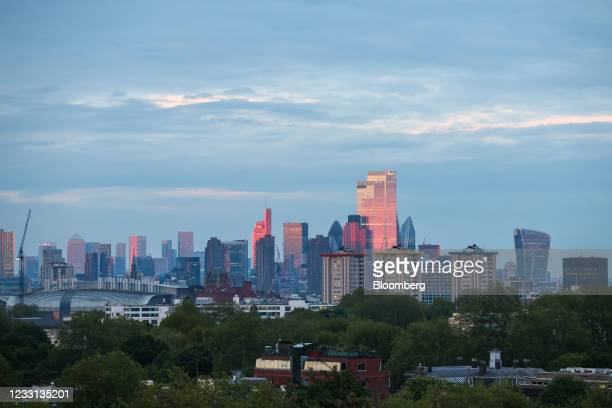 Skyscrapers in the City of London, right, and the Canary Wharf business, financial and shopping district, left, ahead of the supermoon in London,...