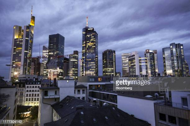 Skyscrapers including the Commerzbank AG headquarters, left, and twin tower headquarters of Deutsche Bank AG, right, stand illuminated at sunrise in...