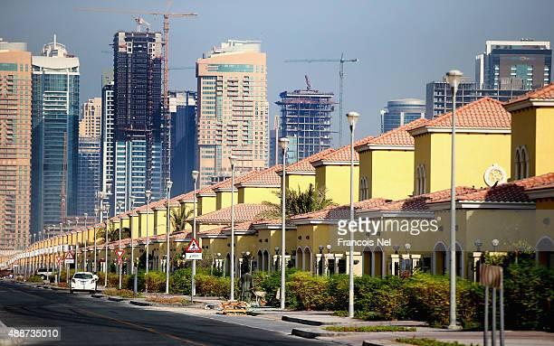 Skyscrapers is seen behind residential villas in Jumeirah Park on September 15 2015 in Dubai United Arab Emirates
