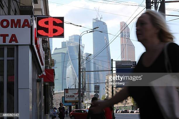 Skyscrapers of the Moscow City business district stand beyond a foreign currency exchange bureau displaying a US dollar sign in Moscow Russia on...