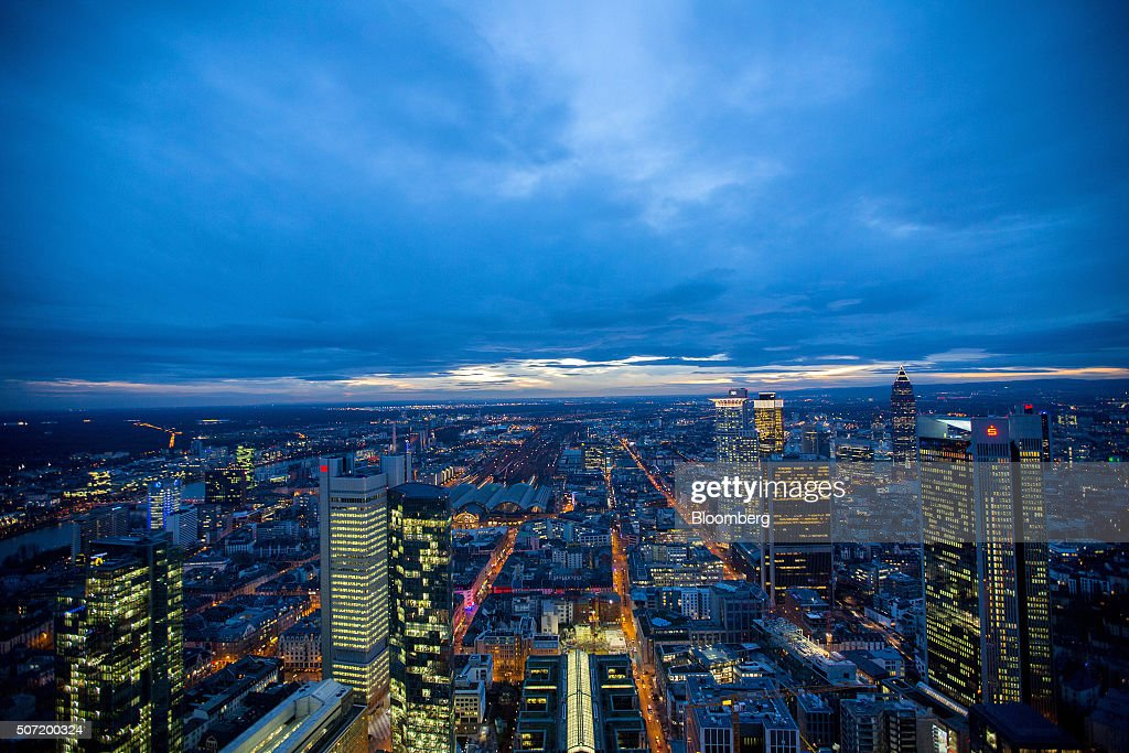Skyscrapers stand illuminated on the city skyline at dusk in Frankfurt, Germany, on Wednesday, Jan. 27, 2016. German domestic demand, buoyed by a stable labor market and low oil prices, will propel the country's economic growth this year and compensate for slowing exports as emerging economies stumbles. Photographer: Krisztian Bocsi/Bloomberg via Getty Images