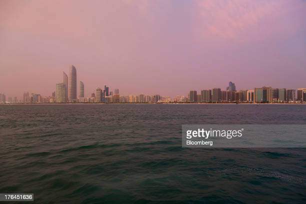 Skyscrapers stand on the city skyline at dusk in Abu Dhabi United Arab Emirates on Monday Aug 12 2013 As Dubai recovers from its slump caused by the...