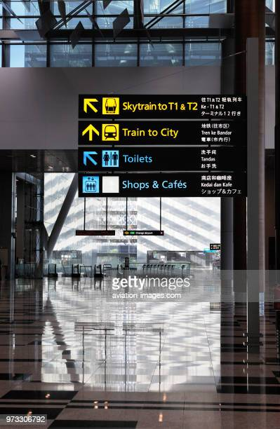 Skytrain Trains to City Toilets Shops and Cafes signs with trolleys behind on the upper level over MRT in Singapore Changi Terminal3