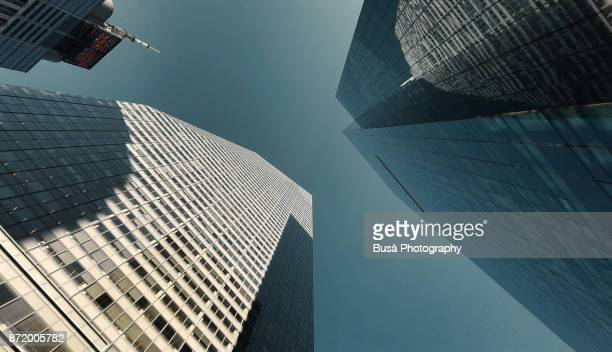 skywards view of skyscrapers in midtown manhattan between 42nd street and 6th avenue, new york city - bryant park stock pictures, royalty-free photos & images