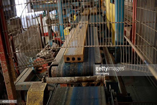 A slab of clay moves down a conveyor belt before being sliced into bricks at the Acme Brick Co manufacturing facility in Leeds Alabama US on Friday...