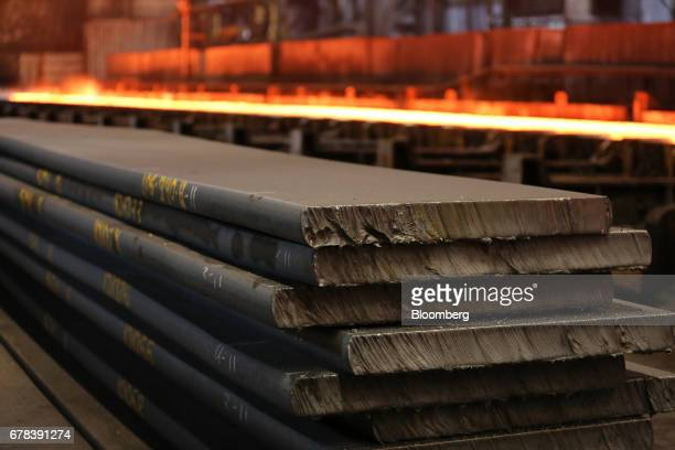 Slabs of cooled iron slabs sit in the rolling shop at the Cherepovets Steel Mill operated by Severstal PJSC in Cherepovets Russia on Tuesday May 3...