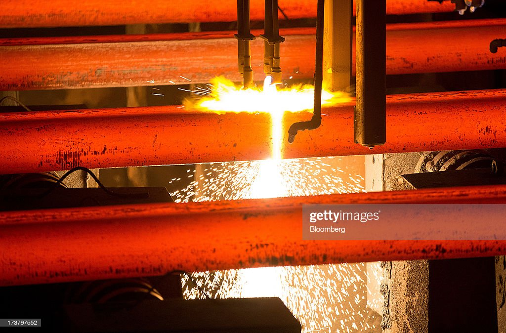 Slabs of red hot steel pass through a heat source on the production line at OAO Mechel's metallurgical plant in Chelyabinsk, Russia, on Wednesday, July 17, 2013. Mechel, the country's largest producer of coking coal for steelmakers has begun operating its $700m rail production line which can produce 100 meter rails. Photographer: Andrey Rudakov/Bloomberg via Getty Images