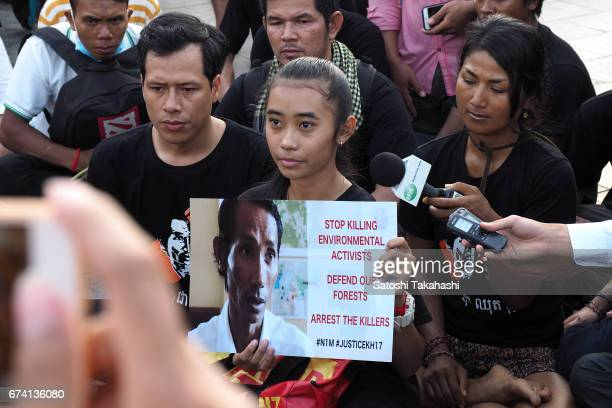 Slain prominent environmental activist Chut Wutty's daughter holds a poster of her father during a commemoration rally for the fifth anniversary of...
