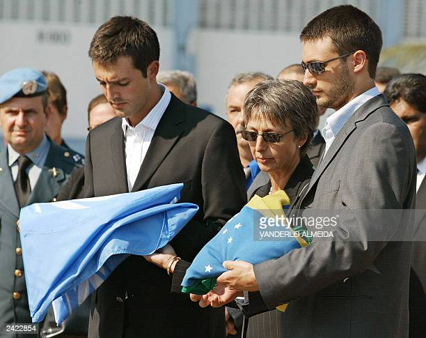 Slain UN diplomat Sergio Vieira de Mello's sons Adrian and Bernard and widow Annie receive the the Brazilian and UN flags, during a funerary ceremony...