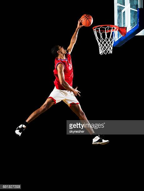 Slam dunking the ball.