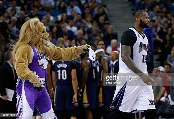 Slamson the Lion the Sacramento Kings mascot tries to give DeMarcus Cousins back his head band after it fell off during their game against the New...