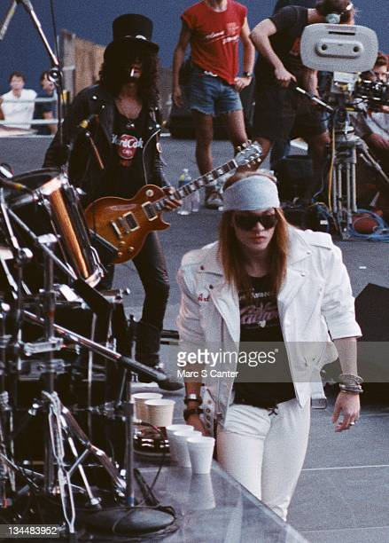 Slash and Axl Rose of the rock group 'Guns n' Roses' open for Aerosmith and Deep Purple as they performs onstage at Giants Stadium on August 16 1988...
