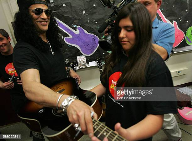 Slash the lead guitarist from Guns N Roses hands autographed guitar to sutdent Christian Alverez 13 after he played guitar with youngsters from the...