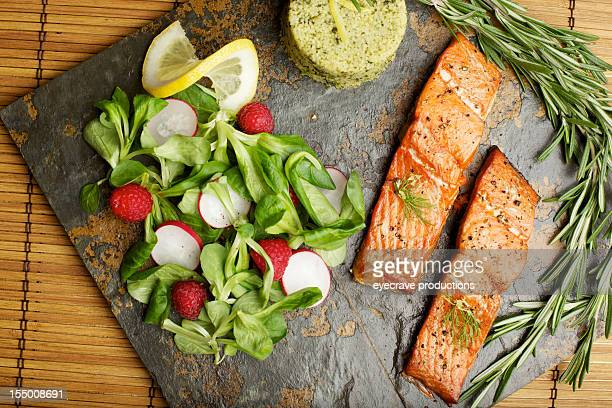 Slate tile plated grilled wild Salmon fillet arugula and couscous