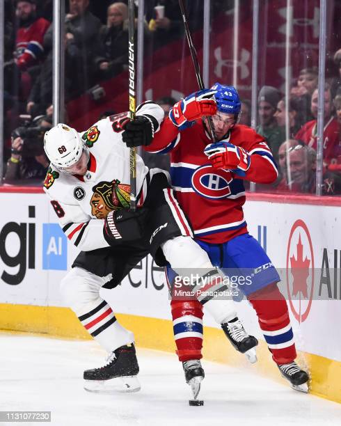 Slater Koekkoek of the Chicago Blackhawks and Jordan Weal of the Montreal Canadiens battle for the puck during the NHL game at the Bell Centre on...