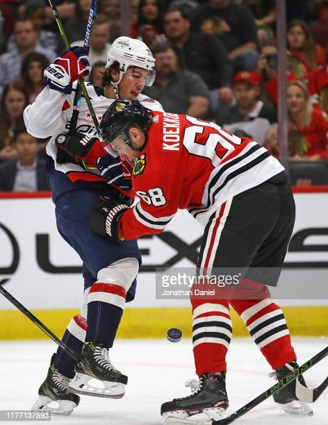 Slater Koekkoek of the Chicago Blackhawks hits T.J. Oshie of the Washington Capitals as they battle for the puck during a preseason game at United...