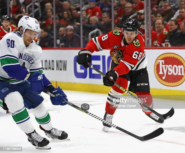 Slater Koekkoek of the Chicago Blackhawks passes the puck around Markus Granlund of the Vancouver Canucks at the United Center on March 18 2019 in...