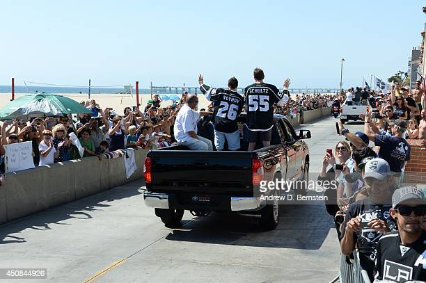Slava Voynov and Jeff Schultz of the Los Angeles Kings wave to fans during the Los Angeles Kings South Bay Victory Parade on June 18 2014 in Hermosa...