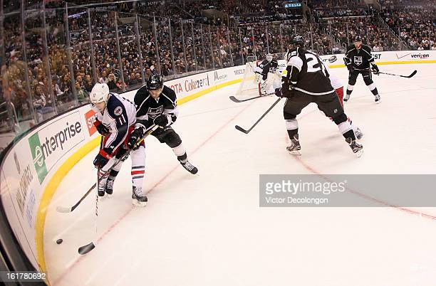 Slava Voynov of the Los Angeles Kings and Matt Calvert of the Columbus Blue Jackets vie for the puck in the corner during the NHL game at Staples...
