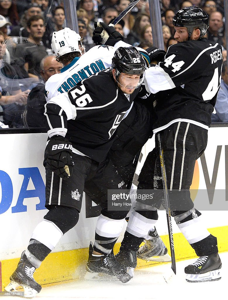 Slava Voynov #26 of the Los Angeles Kings and Robyn Regehr #44 pin Joe Thornton #19 of the San Jose Sharks into the boards during the second period in Game Six of the First Round of the 2014 NHL Stanley Cup Playoffs at Staples Center on April 28, 2014 in Los Angeles, California.