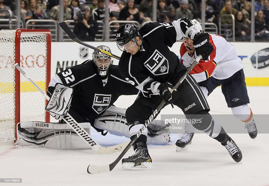 Slava Voynov #26 of the Los Angeles Kings is pursued by Stephen Weiss #9 of the Florida Panthers for the puck as goaltender Jonathan Quick defends his net in the third period at Staples Center on December 1, 2011 in Los Angeles, California. The Kings defeated the Panthers 2-1.