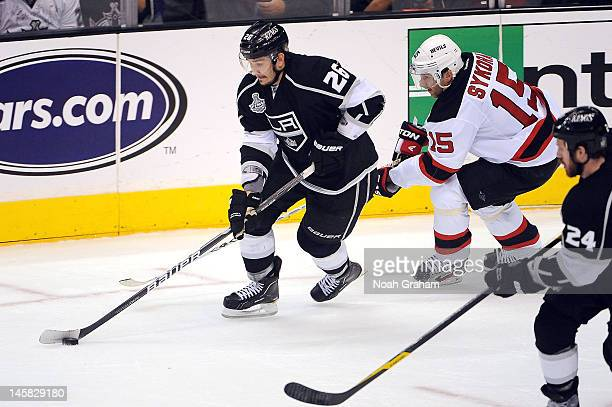 Slava Voynov of the Los Angeles Kings skates with the puck against Petr Sykora of the New Jersey Devils in Game Four of the 2012 Stanley Cup Final at...