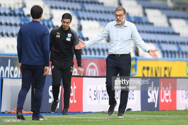 Slaven Bilic Manager of West Bromwich Albion speaks to Danny Cowley Manager of Huddersfield Town during the Sky Bet Championship match between...