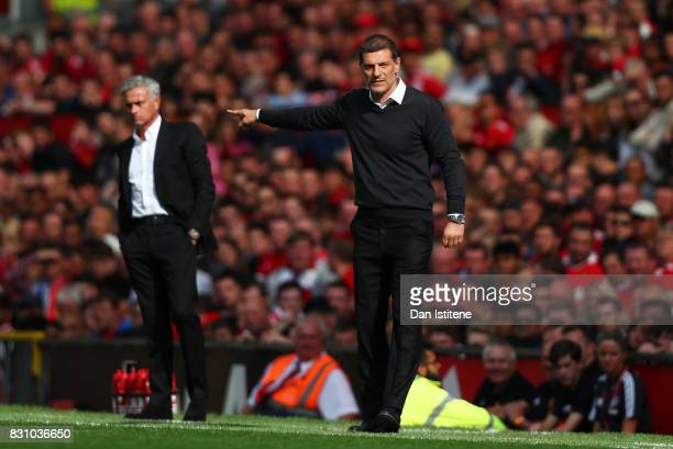 Slaven Bilic Manager of WestHam United gives his team instructions as Jose Mourinho Manager of Manchester United looks on during the Premier League...