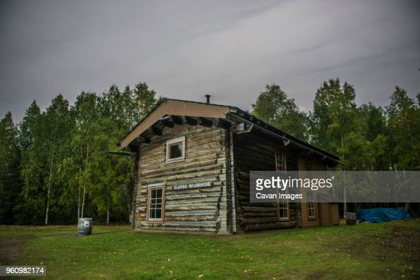 slavens roadhouse on field by trees at yukon_charley rivers national preserve against cloudy sky - charley green stock pictures, royalty-free photos & images