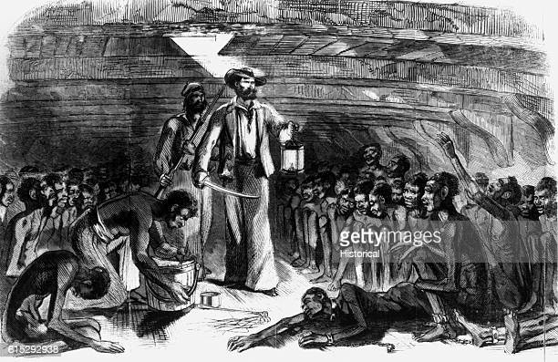A slaver walks among his African slaves in the hold of the slave ship Gloria