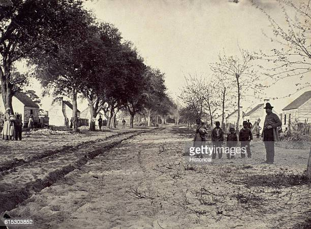 Slaves stand in front of their quarters on General Thomas F Drayton's plantation on Hilton Head South Carolina 1862