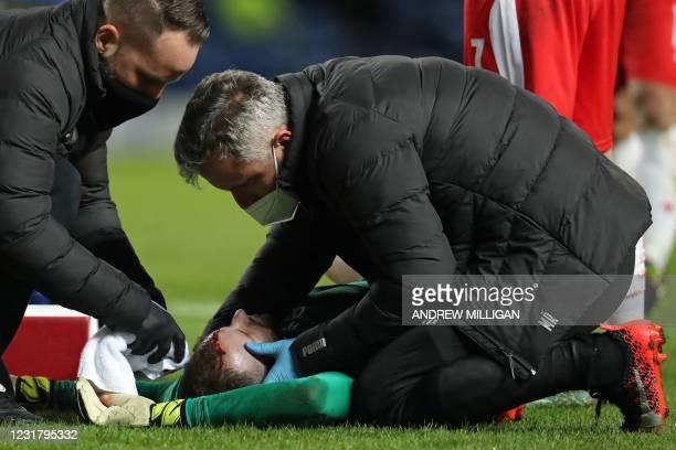 Slavia Prague's Czech goalkeeper Ondrej Kolar receives medical attention after being hurt in a collision with Rangers' English striker Kemar Roofe...