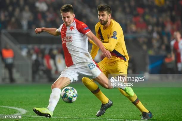 Slavia Prague's Czech midfielder Lukas Masopust and Barcelona's Spanish defender Gerard Pique vie for the ball during the UEFA Champions League...