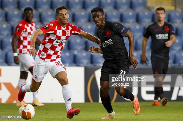 Slavia's midfielder Ibrahim Traore is marked by Hapoel's defender Mariano Bareiro during the UEFA Europa League group C football match between...