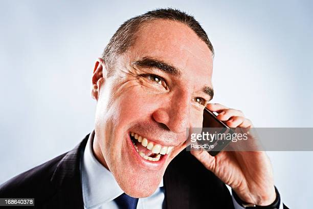 sleazy man tries too hard, giving cheesy grin on phone - con man stock photos and pictures