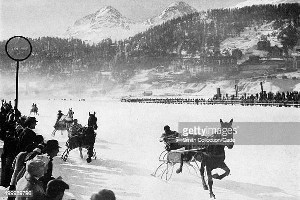 Sled racing on the lake of Saint Mortiz men riding on sleds pulled by horses a crowd gathering to watch Switzerland 1922