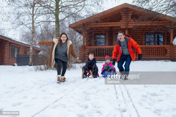sledding with their family - ski holiday stock photos and pictures