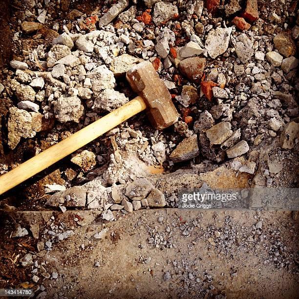 Sledge hammer lying in rubble