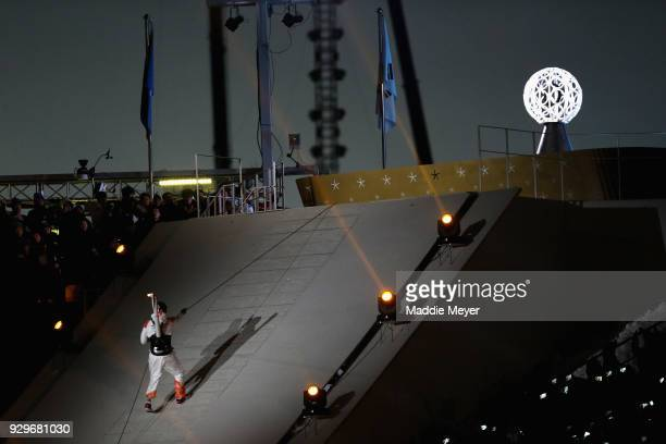 Sledge hockey player Han Min Su of South Korea climbs via rope with the torch during the opening ceremony of the PyeongChang 2018 Paralympic Games at...