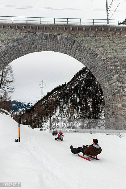 sledgers sliding down on trail - merten snijders stockfoto's en -beelden