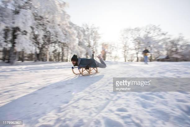 rodeln auf schnee in verschwommener bewegung! - schlitten stock-fotos und bilder