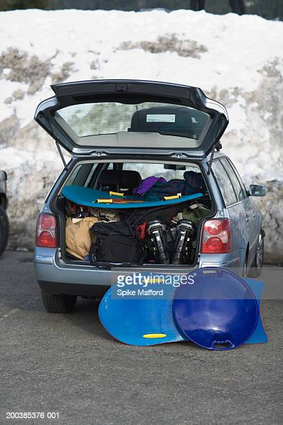 Sleds, ski gear and bags in back of car, hatchback open