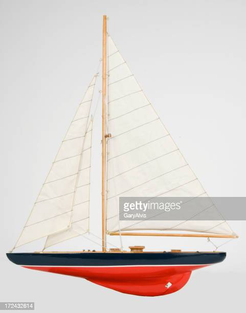Sleek black and red single masted sailboat-isolated on white