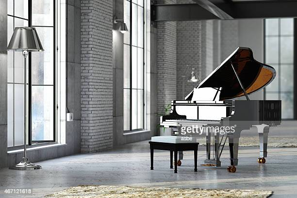 sleek black grand piano in well lit room - loft stock photos and pictures