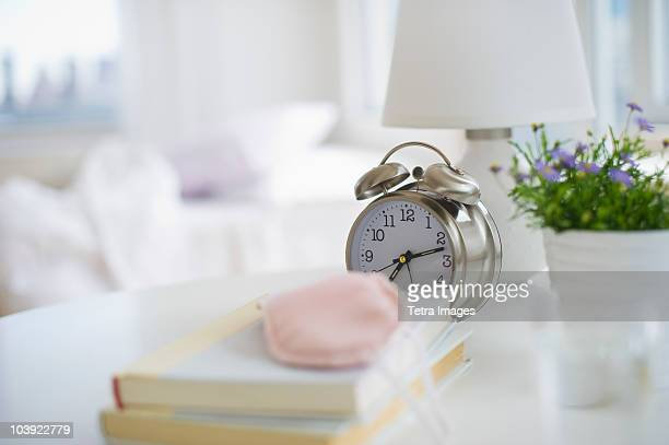 Sleep mask books and alarm clock on bedside table