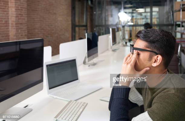sleeping and tired businessman working on computer - myopia stock photos and pictures