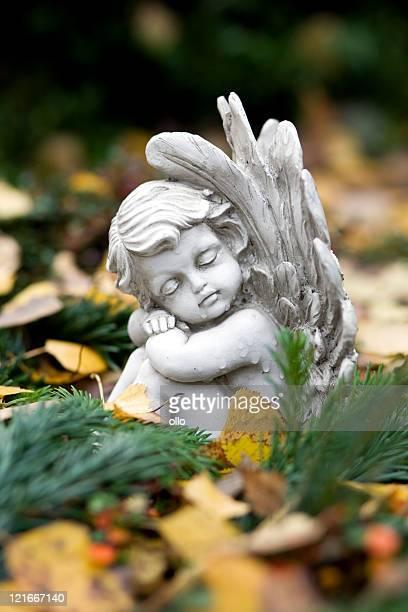 Sleeping angel sitting on a grave
