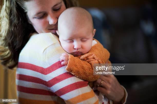 Schlafendes Babymädchen in den Armen ihrer Mutter