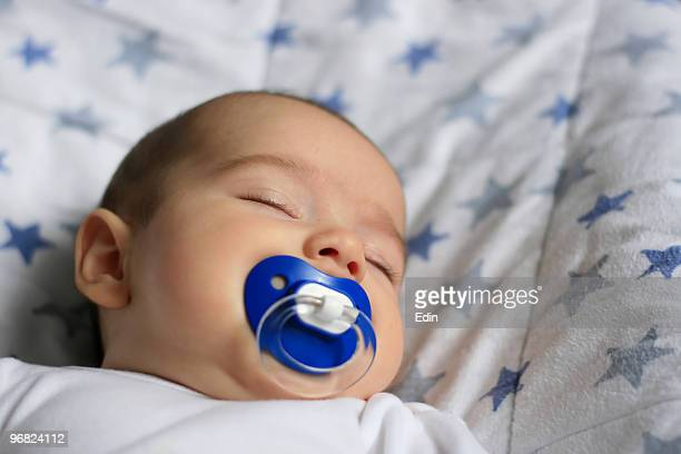 Sleeping baby with a blue pacifier