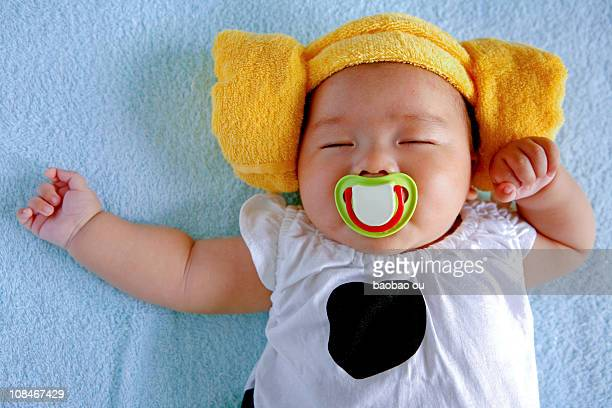 sleeping baby with nipple in the mouth